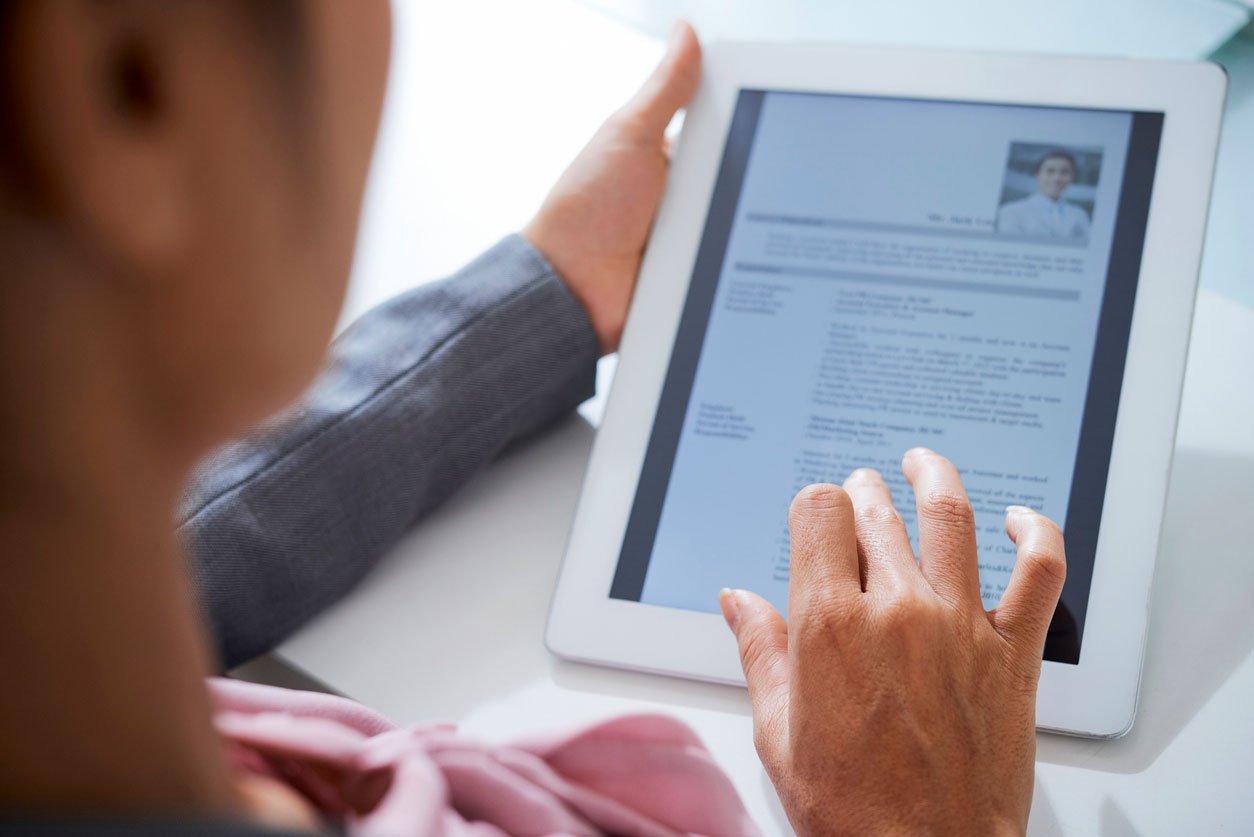 En dame jobber med CV'en sin på et nettbrett